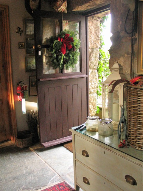 Door welcomingly open dressed with Christmas wreath