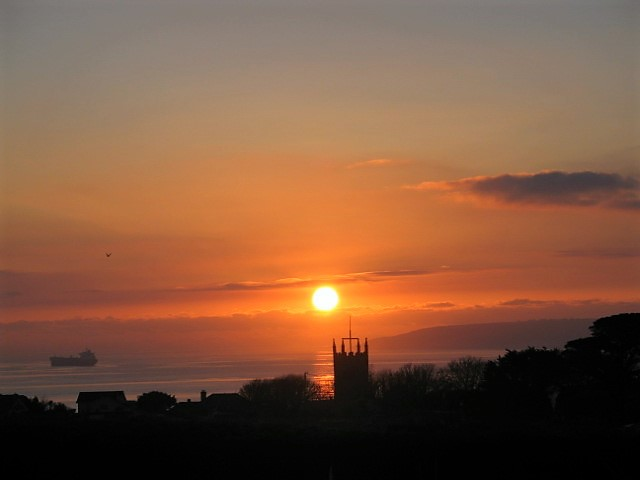 Explore Cornwall - Sunset with village silhouette against sea