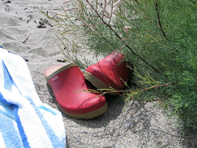 Shoes kicked off on a sandy beach