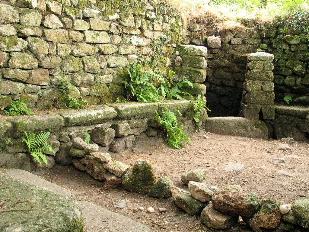 The interior of Madron chapel and stone benches lining the walls of a celtic chapel