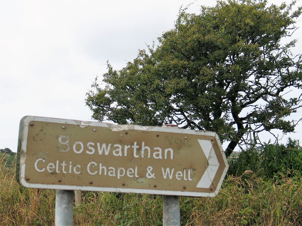 The battered brown signs reads Boswarthen Celtic Chapel & Well pointing to Madron sacred Well and Chapel