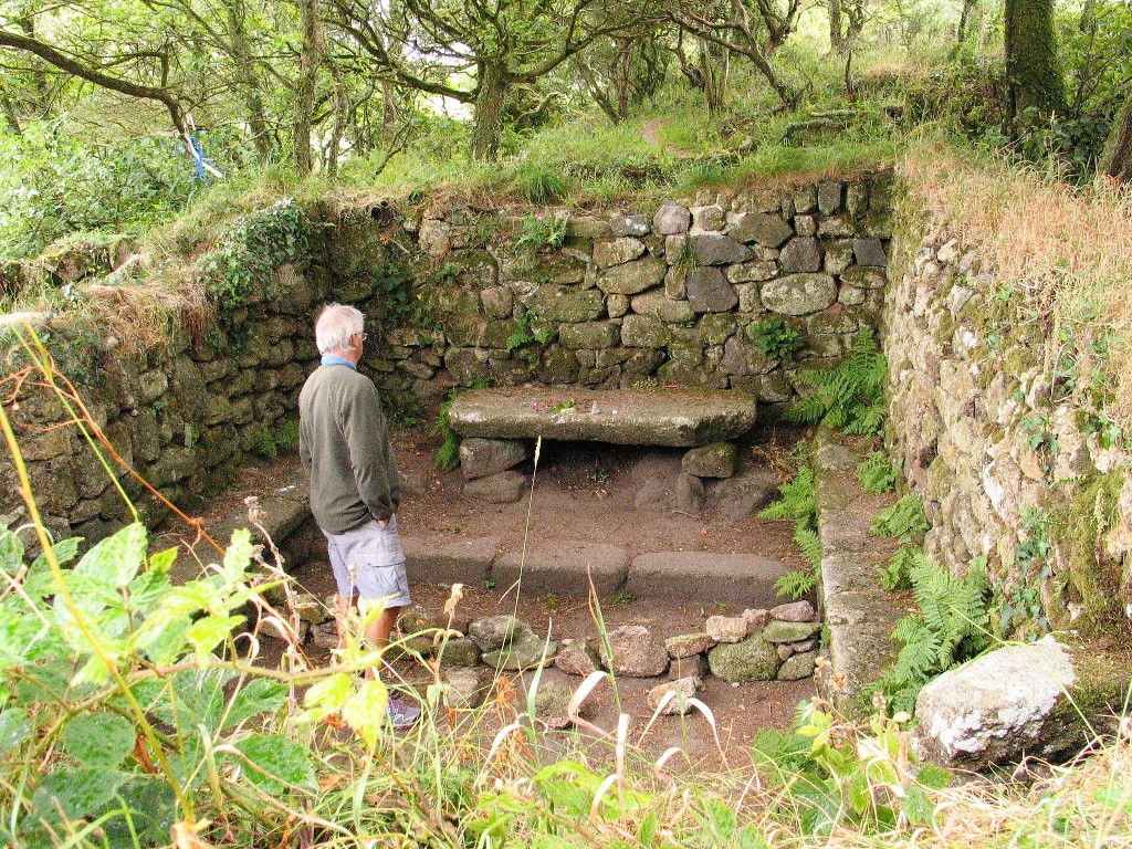 Man standing within the ruins of a roofless stone building that is Madron celtic chapel