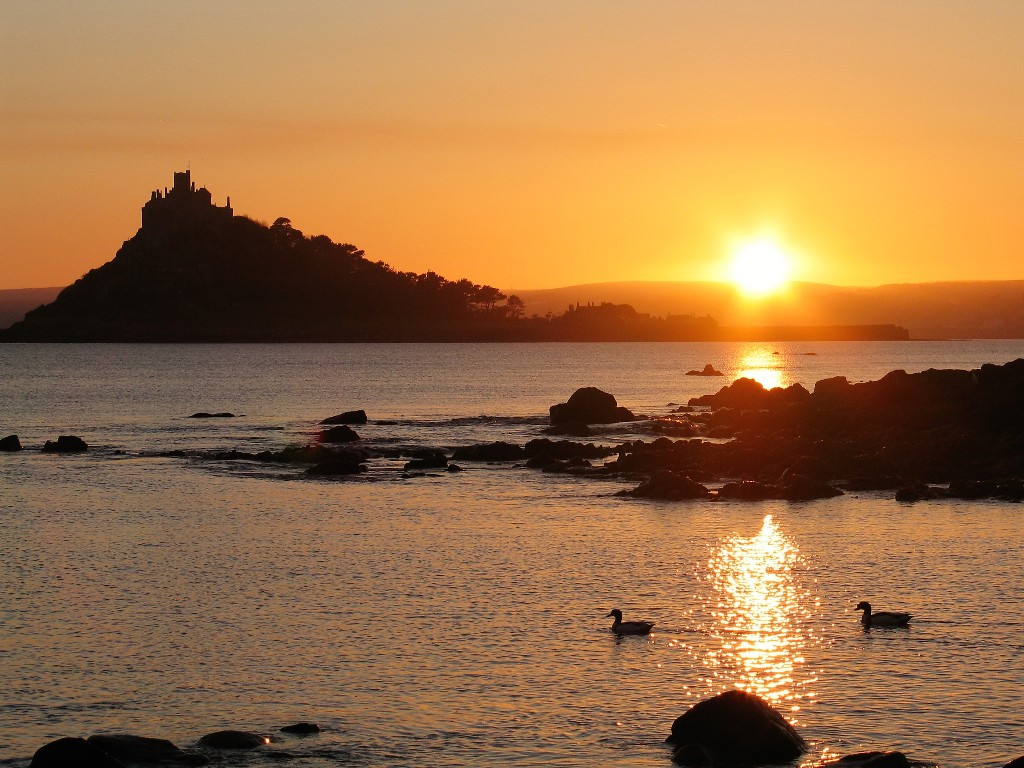 A tranquil sunset over St Michael's Mount and Penzance wtih ducks on the sea