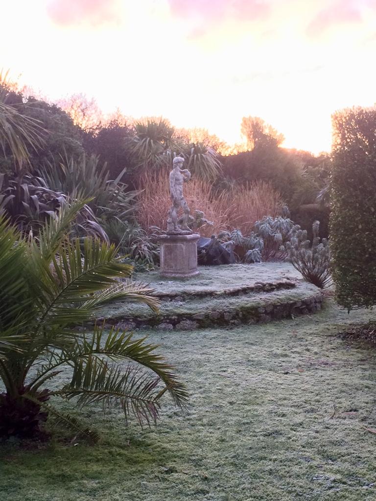 Romantic winter frost in Italian garden backed by grasses