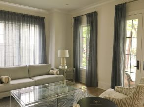 Grey curtains on metal rods, unlined sheer panels,