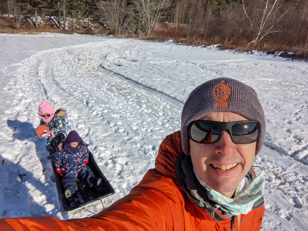 Richard Byrne walking in snow and pulling a sled with two children in it.