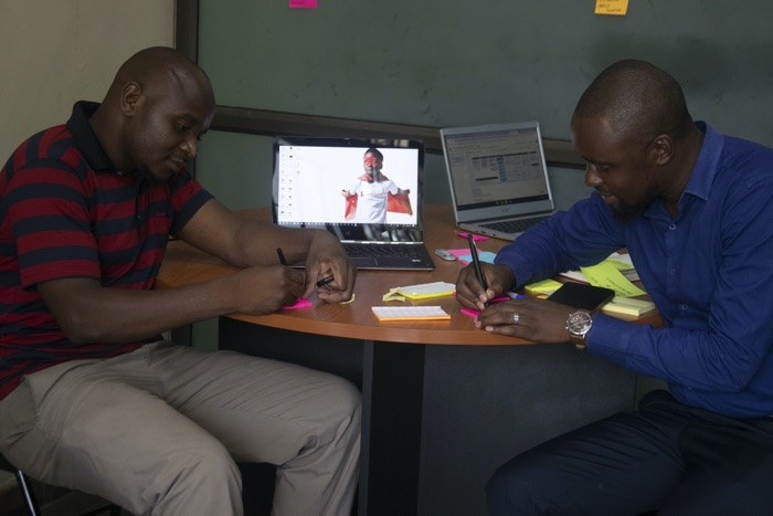 The Padziwe team writing ideas on post-it notes