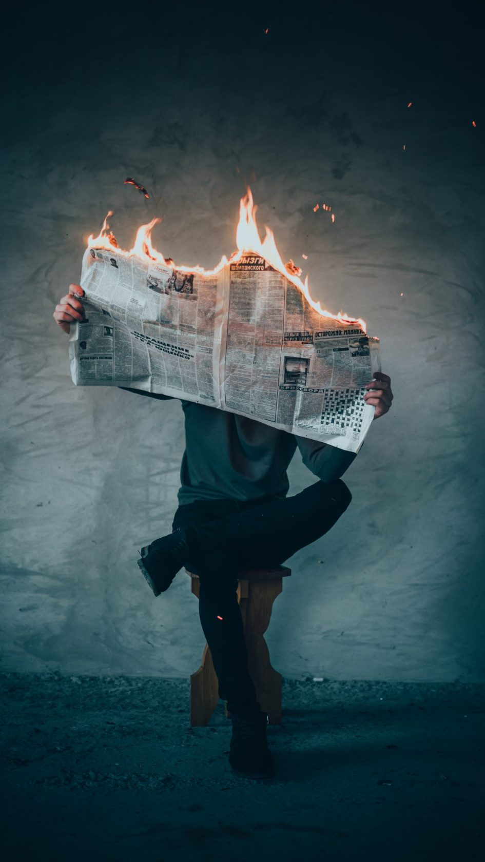 person holding newspaper that is burning