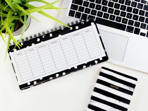 Photo of a weekly planner laying on top of a laptop