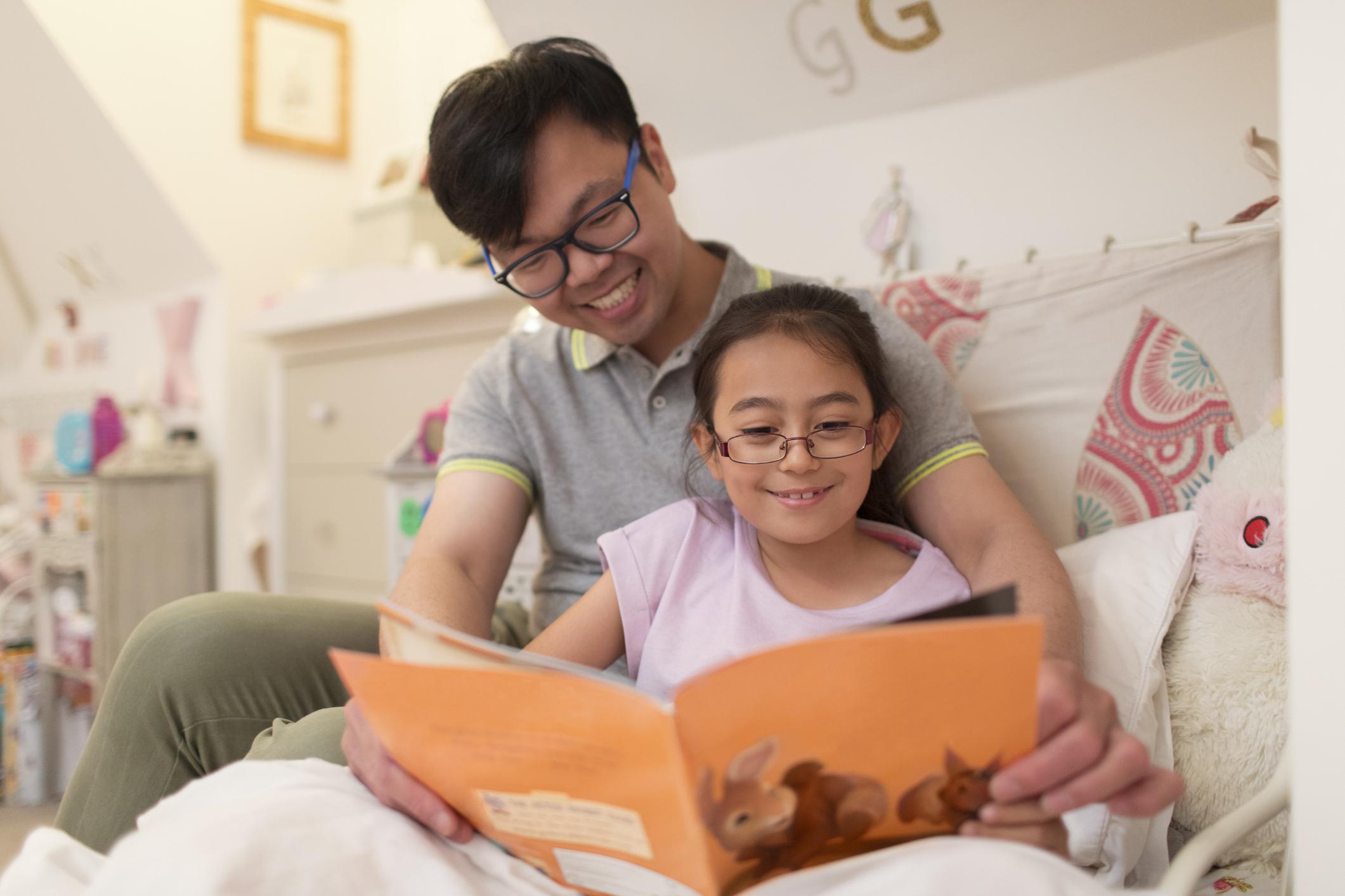 Seorang ayah sedang membacakan buku belajar bahasa Inggris anak untuk puterinya - Edu2Review