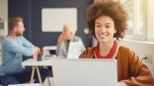 Moça sentada em frente a um notebook elaborando o marketing escolar