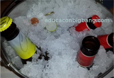 Botella y moneda enfriándose en cubo con hielo