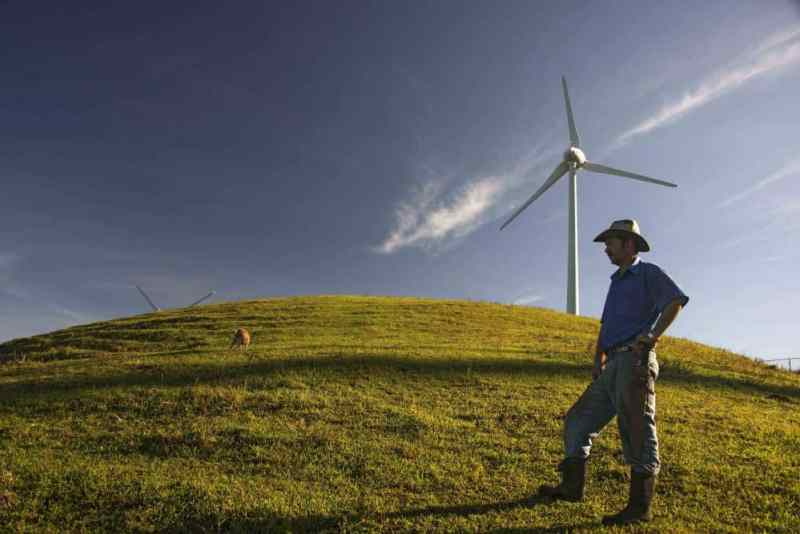 A farmer stands near a wind mill of the National Power and Light Company in Santa Ana, Costa Rica, on Oct. 23, 2015.