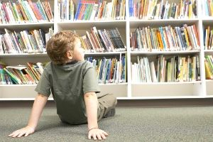 Deschooling - child sitting on library floor
