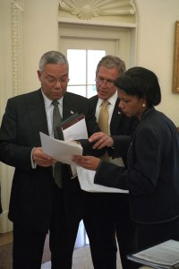 President George W. Bush looks over a brief with Secretary of State Colin Powell and National Security Adviser Condoleezza Rice in the Oval Office
