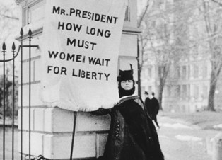 """Woman holding a flag that reads """"Mr. President How Long Must Women Wait for Liberty"""""""