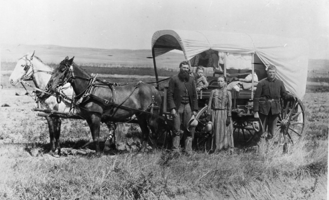 Family with covered wagon and horses