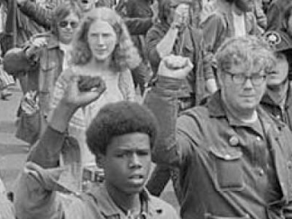 Young adults marching and protesting with fists raised