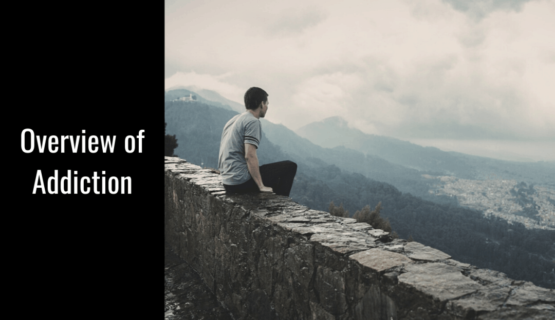 A man sits overlooking the valley and contemplates his online addiction counseling training