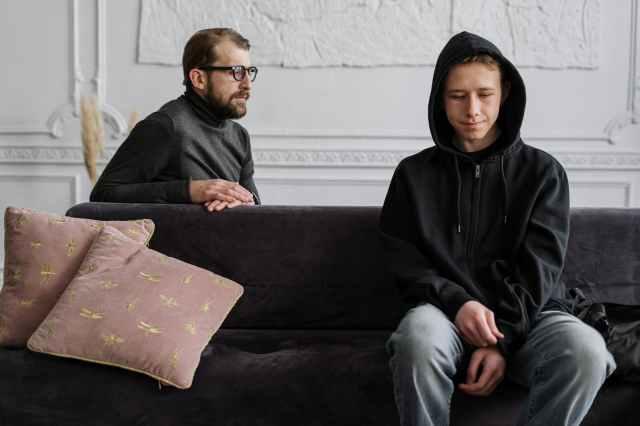 man in black hoodie sitting on brown couch