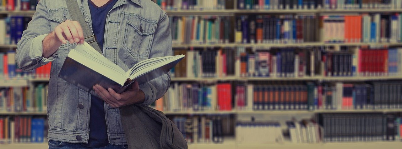 Young man reading a textbook in a library