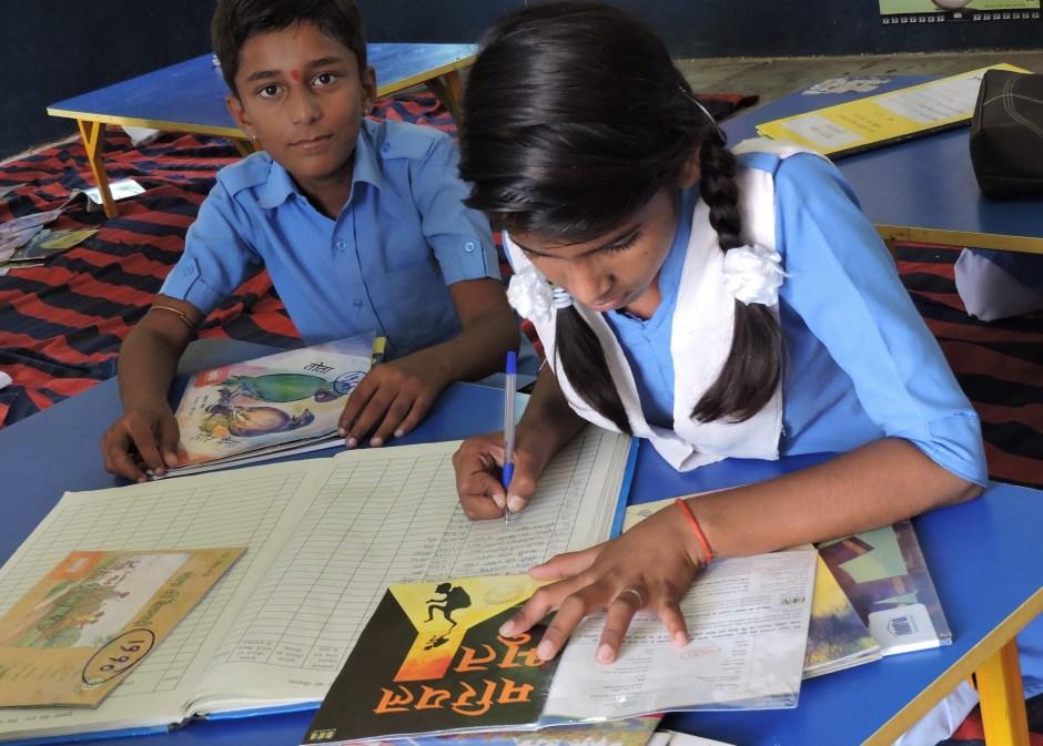 लायब्रेरी में अपने साथ के बच्चों को किताबें इश्यू करते छात्र।