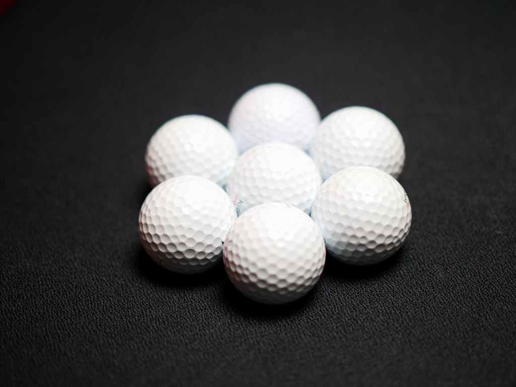 set of golf balls on black background