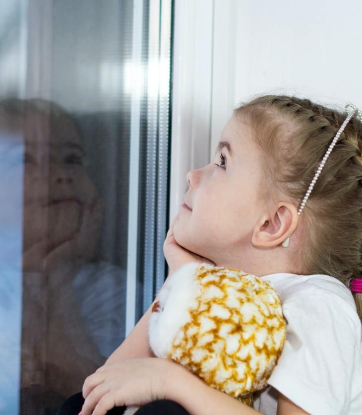 Une enfant regarde à la fenêtre. Un parent adoptant une orientation mentale pourrait commenter sur le fait que l'enfant regarde dehors parce qu'elle voit un oiseau qu'elle trouve beau.