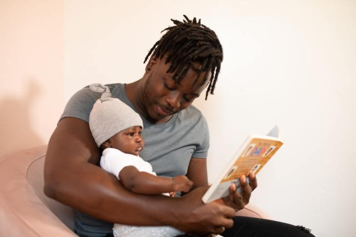 Un père lit un livre à son enfant. La lecture active et participative est une des façons qui peut soutenir le développement du langage.