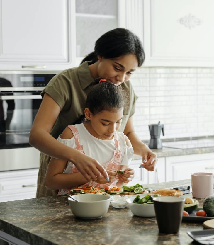 Une fillette aide sa mère à préparer à souper. Les enfants qui aident leur parent dans diverses tâches quotidiennes seront plus portés à aider les autres et coopérer avec leurs pairs.