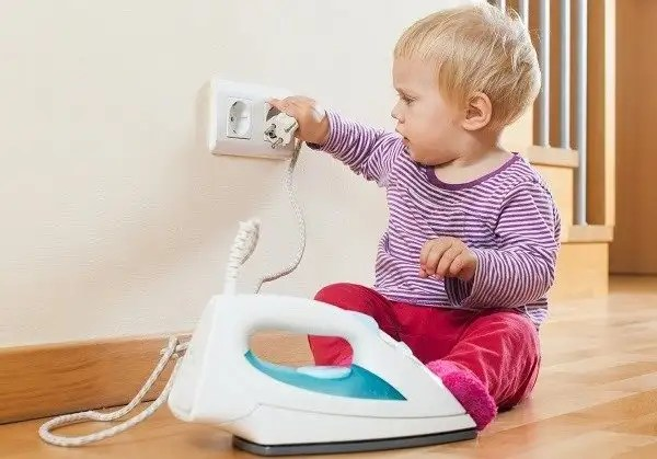 Toddler playing with electrical appliances