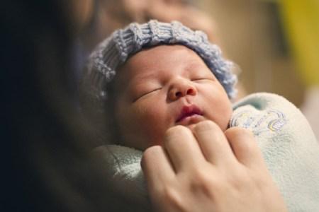 Bébé qui dort dans les bras de sa maman, sa figure d'attachement principale