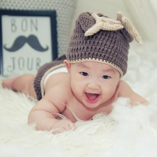 Bébé sourit sur sa peau d'agneau