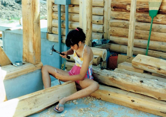 Jenn, 13, chiseling out the holes for the electrical boxes in the logs for the house