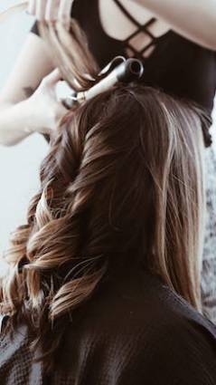 A women with beautiful braun hair gets her hair curled with professional hair products