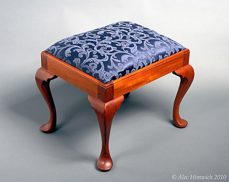 This Queen Anne style footstool incorporates padfoot style cabriole legs that are hand cut and hand carved. It is modeled after a pieced in the Winterthur Museum. The upholstery is foam with cotton lining and brocade covering. The wood is Honduran mahogany with shellac finish.