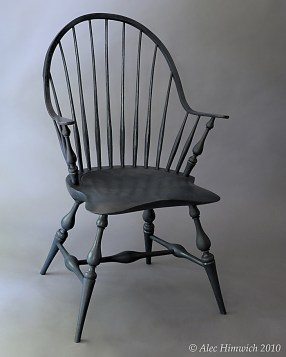 Windsor chairs were popular in the 18th and 19 centuries and are seeing a resurgence in interest. The unique feature of this continuous arm Windsor chair is the double curve arm which constitutes the back and arms of the chair. Pine is used for the seat; red oak, for the spindles; white oak, for the continuous arm; and maple, for the arm posts and baluster leg turnings. The finish is milk paint (Soldier Blue), and tung oil.