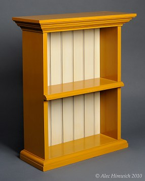 This wallhung shelf is made completely with hand tools including the joinery and molding. The back is tongue and grooved and beaded. The shelf is designed to be hung from the wall with a French cleat. The wood is radiata pine and the finish is milk paint (mustard yellow and cream).