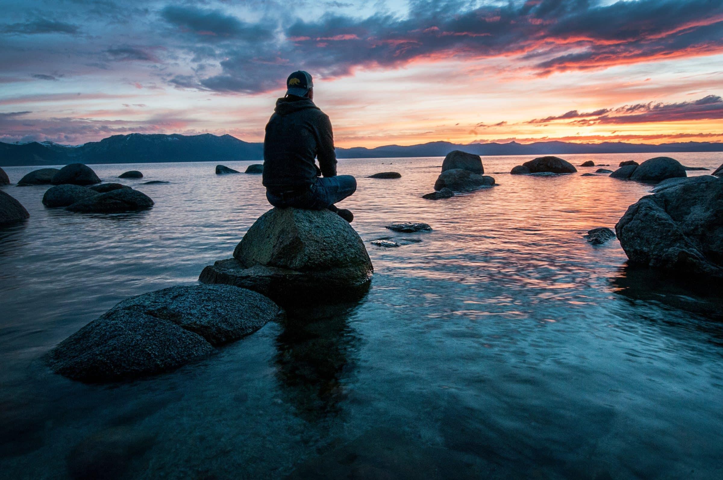 Man mediterend op rots die uitkijk over mooie horizon van ondergaande zon