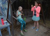 Harmony and Cali laugh as they blow bubbles in the backyard of the family's home.