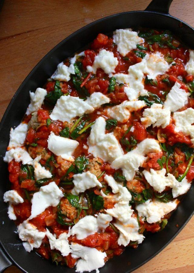 Mozzarella over tomatensaus verdelen / www.eenlepeltjelekkers.be