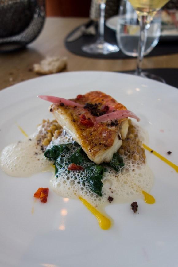 rouget, épeautre, épinards et chorizo sur une assiette blanche