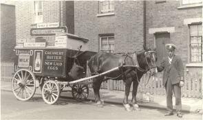United Dairies milkman in uniform posing on street