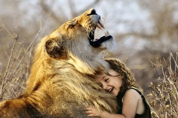 Niña sonriendo abrazada a león