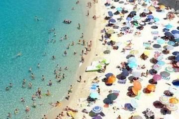 Una playa con decenas de sombrillas clavadas en la arena