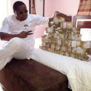 A Party Official poses with Bundles of Money (Photo)