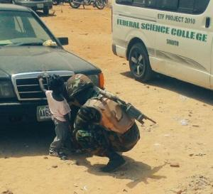 Photo Of The Day – A Gallant Nigerian Soldier help a little Girl Tie Her Shoes