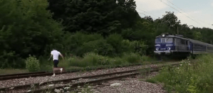 Daredevil jokes with death as he jumps in front of a fast train (Video)