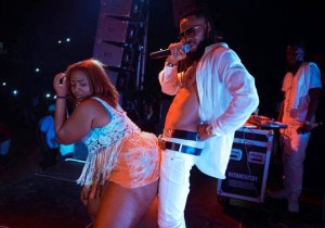 Flavour grinds a half clothed plus size woman on stage in Liberia