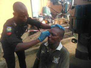 Police Officer giving First-Aid to a Danfo Driver who was beaten by passengers (Photos)